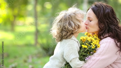 Mother and child with bouquet of flowers in autumn park