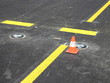 Yellow stripes with one traffic cone