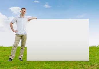 Man standing in a field with a large blank sign