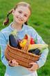 Vegetable garden - lovely girl with basket of vegetables