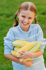 Vegetable - lovely girl with corn on the cob in the garden