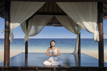 Beautiful yoga woman at luxury beach resort