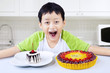 Boy laughing before eating birthday cakes at home