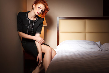 Attractive young adult woman sitting on bedside table in hotel