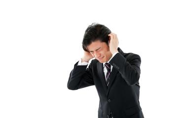 頭を抱えて悩む若いビジネスマン