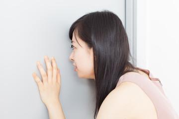 ドアスコープを覗く女性