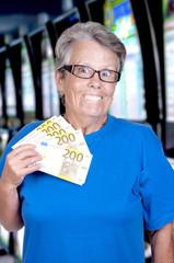 Dame âgée tenant dans la main une liasse de billets.