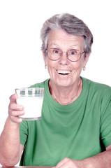 Femme âgée tenant dans la main une verre de lait.