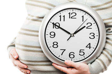 Pregnant woman hand holding large office wall clock showing time