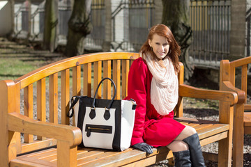 redhaired woman crossing sitting on the bench in park