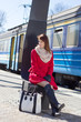 young beautiful woman in red waiting for train on the platform