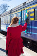 woman in red waving hand on the platform