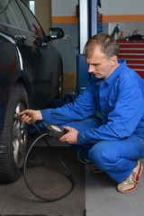 Auto mechanic is checking air pressure in tire