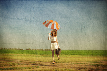 Redhead enchantress with umbrella and suitcase at spring country