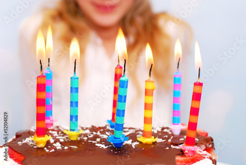 young girl celebrates birthday and blowing candles on the cake