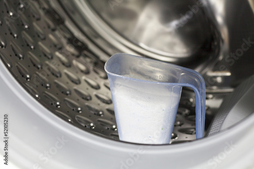 Measuring cup full of detergent in the washing machine