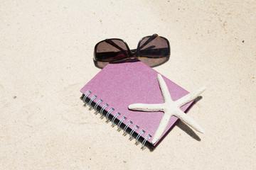 Notebook sunglass and starfish lying on beach