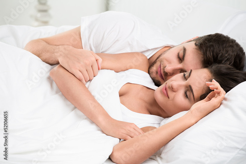 Young adult couple sleeping in bedroom