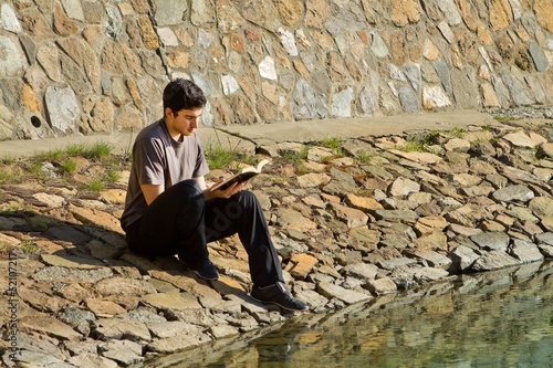 Man Reading Bible By Lake