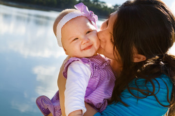 Mom Kissing Baby Daughter By Lake