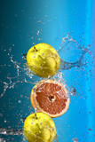 fresh lemons and apple under water jet splash