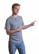 Junger Mann in Jeans und Shirt zeigt die Richtung