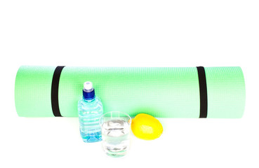 Yoga Mat roll with bottle of water and lemon  isolated on white