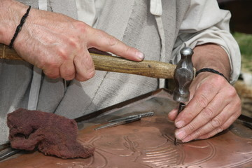 old craftsman Mason during the processing of a copper with an en