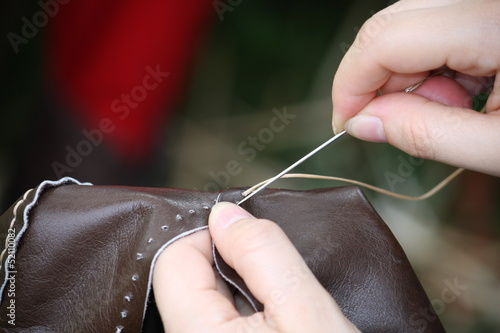 woman while sewing a dress in leather with needle and thread