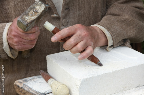 old craftsman Mason during the processing of a piece of white ma