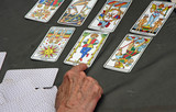a reader's hand during the reading of the playing cards and Taro