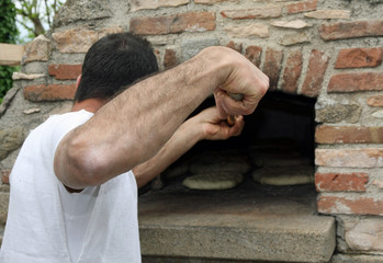 muscled Baker when baking bread in a wood-burning oven