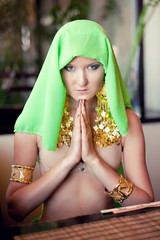Portrait of a young beautiful woman in a prayer position