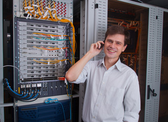 Network engineer in server room talking on the mobile phone