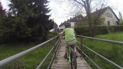 Kind fährt Fahrrad nah vor der Kamera über eine Brücke