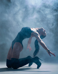 Modern style dancer posing on a studio grey background in fog