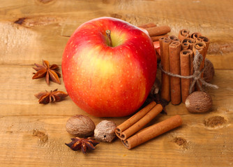 Cinnamon sticks,red apple, nutmeg,and anise on wooden table