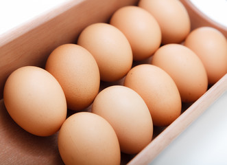 Eggs in wood tray over white background