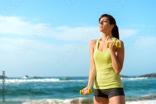Fitness woman training biceps on beach