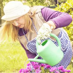 Señora regando flores un dia soleado.