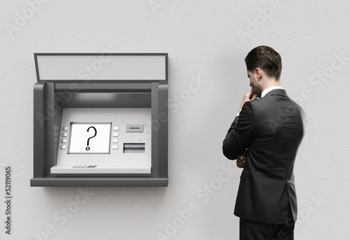 man looking at atm