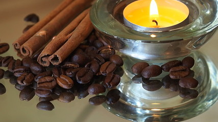Romantic background with coffee beans, cinnamon and candles