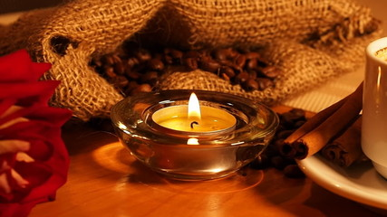 romantic background with candles, a cup of coffee and a rose