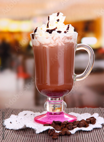 Layered coffee in glass on table on bright background