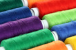 Many-coloured bobbins of thread closeup