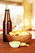 Potato chips and glass bottle with beverage,
