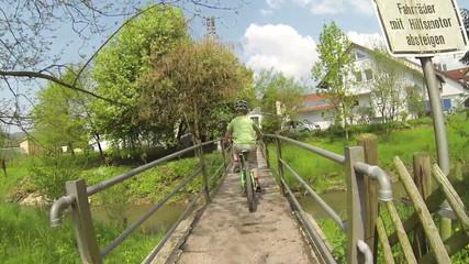 Kind fährt mit dem Fahrrad über eine Brücke