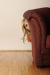 Girl hiding behind sofa