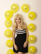 Happy young woman surrounded with smiley face balloons
