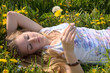 Spring: young woman sleeping between dandelion flowers